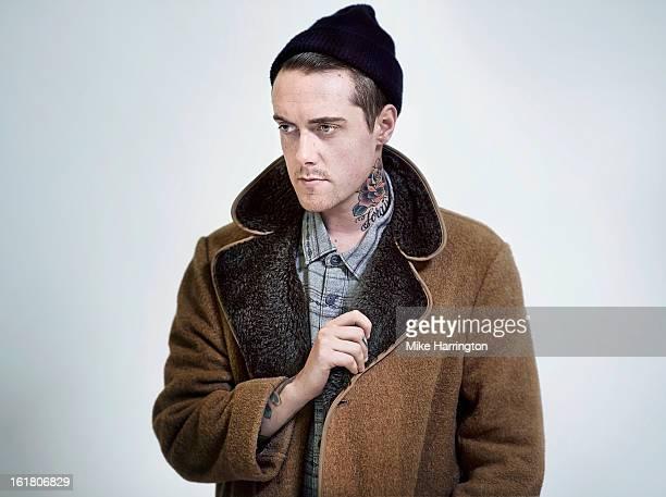 Man with coat and woollen hat looking pensive.