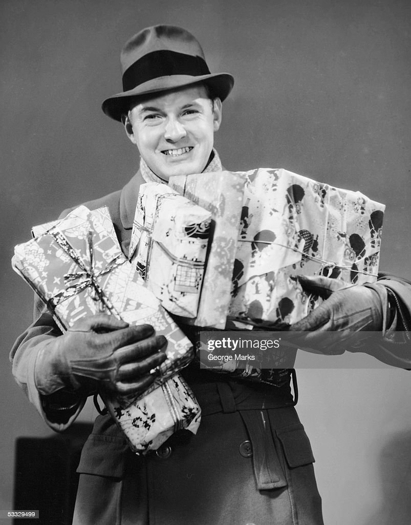 Man with coat, gloves and hat carrying Christmas gifts : Stock Photo