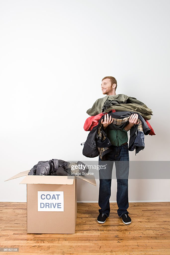 Man with coats for coat drive : Stock Photo