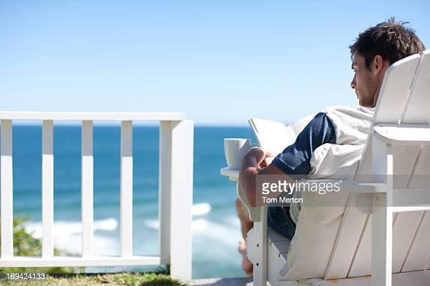 Mann mit Kaffeetasse lesen Buch im Liegestuhl mit Blick auf