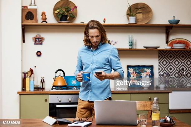 Man with coffee cup texting on smart phone
