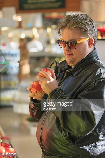 Man with congenital blindness at the grocery store picking out fruit