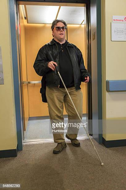 Man with congenital blindness exiting an elevator