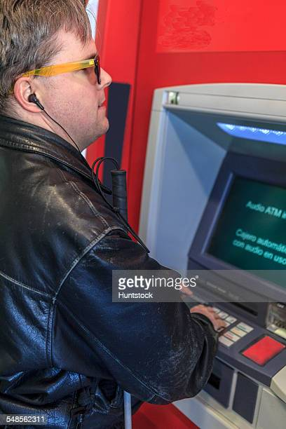 Man with congenital blindness using a bank ATM