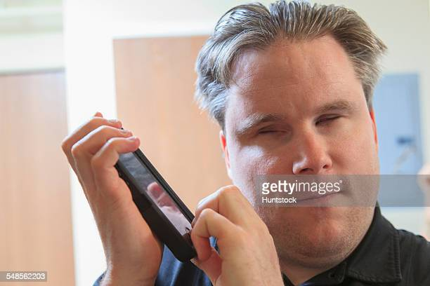 Man with congenital blindness using assistive listening to hear his text messages