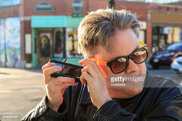 Man with congenital blindness using  assistive technology to listen on the street