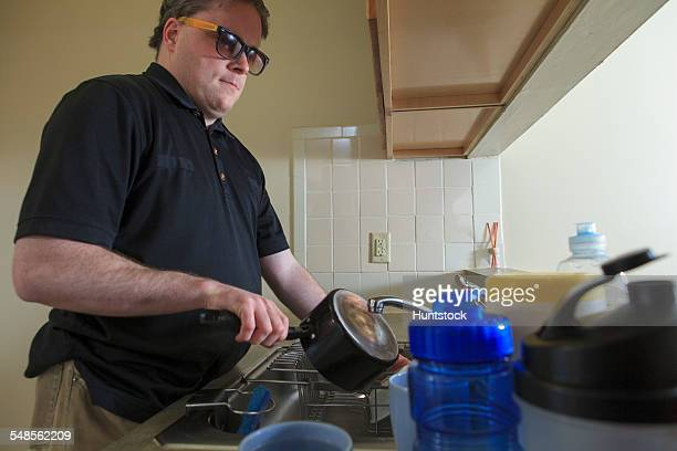 Man with congenital blindness washing dishes in his kitchen
