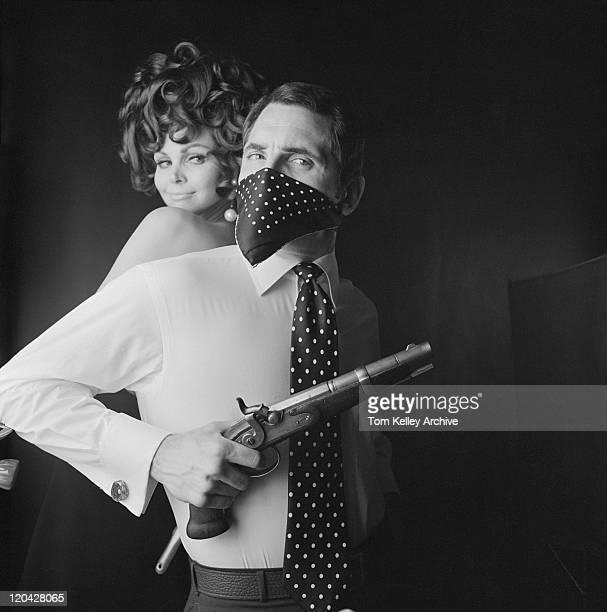 Homme avec une bouche de femme souriante et tenant arme à feu