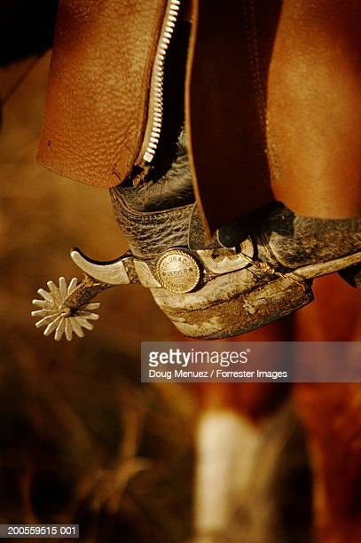 Man with cowboy boots riding horse, close-up