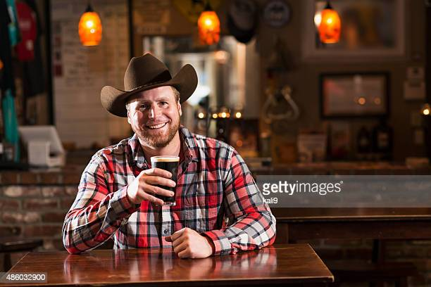 Man with cowboy hat sitting in bar drinking beer