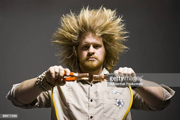 man with crazy hair holding jumper cables