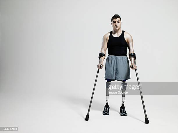 Man with crutches and prosthetic legs