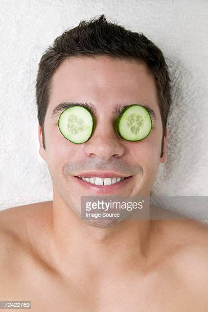 Man with cucumber slices on his eyes