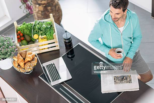 Man with cup of coffee, laptop and newspaper in the kitchen