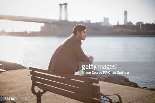 Man with cup of coffee on park bench : Stock Photo