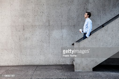 man with cup of coffee walking down concrete stair : Stock Photo