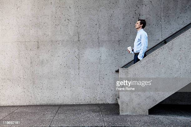 man with cup of coffee walking down concrete stair