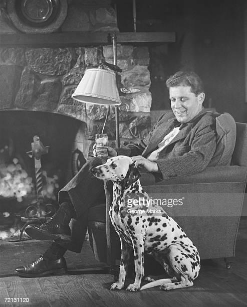 Mann mit Dalmatiner sitzen am Kamin (B & W