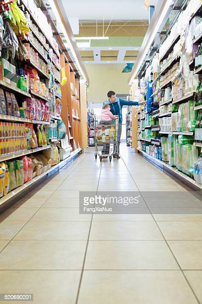 Man with daughter in trolley in supermarket aisle, full length