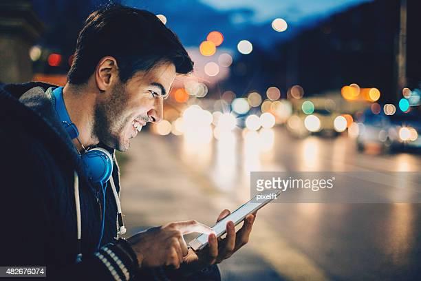 Uomo con digital tablet e cuffie, all'aperto di notte del traffico