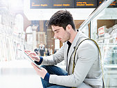 man with digital tablet at train station