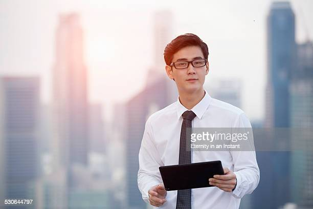Man with digital tablet in front of buildings