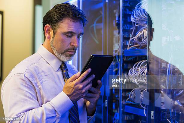 Man with digital tablet in server room