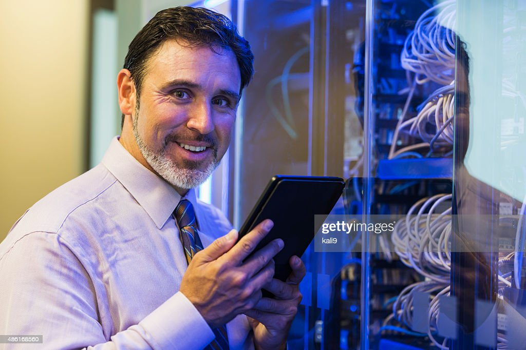 Man with digital tablet in server room : Stock Photo