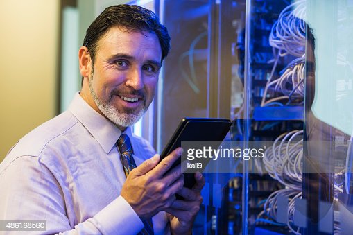Man with digital tablet in server room