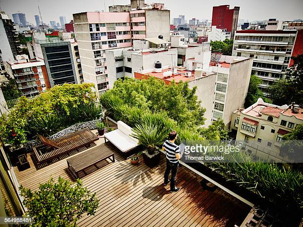 Man with digital tablet on rooftop terrace of home
