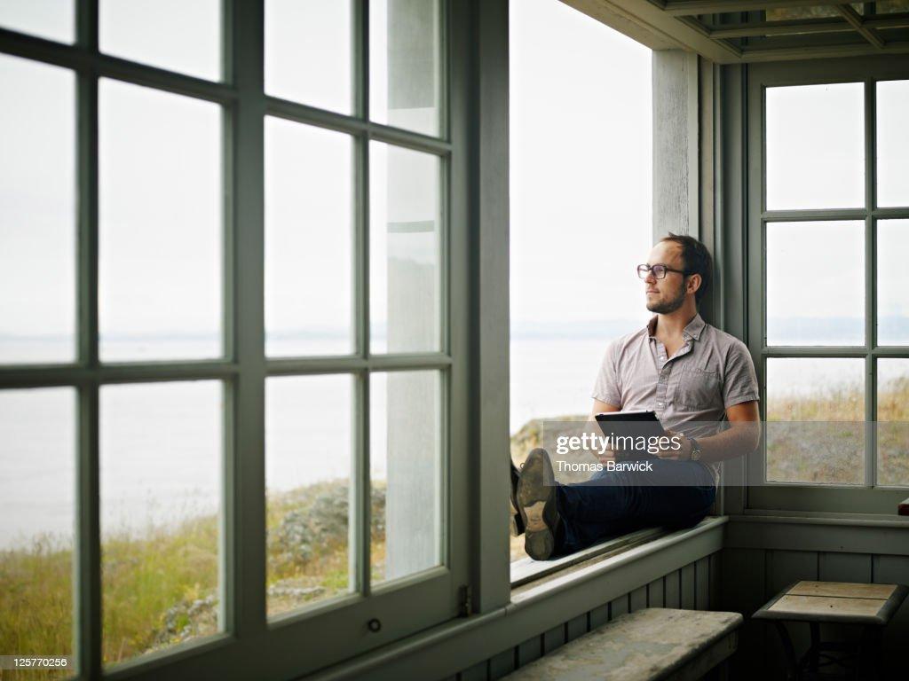 Man with digital tablet sitting on window ledge : Stock Photo
