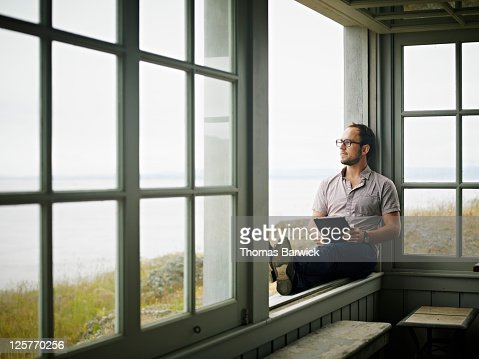 Man With Digital Tablet Sitting On Window Ledge Stock Photo | Getty Images