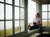 Man with digital tablet sitting on window ledge