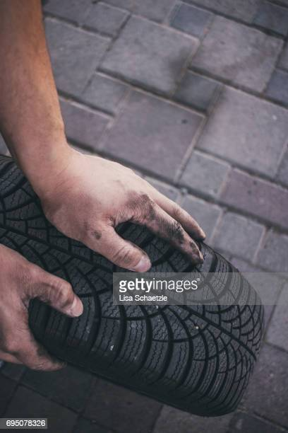 Man with dirty hands holding a tire