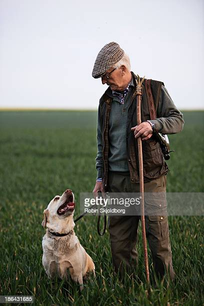 Man with dog and walking stick in field