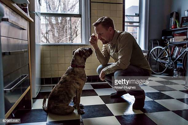 Man with dog both sitting in Kitchen