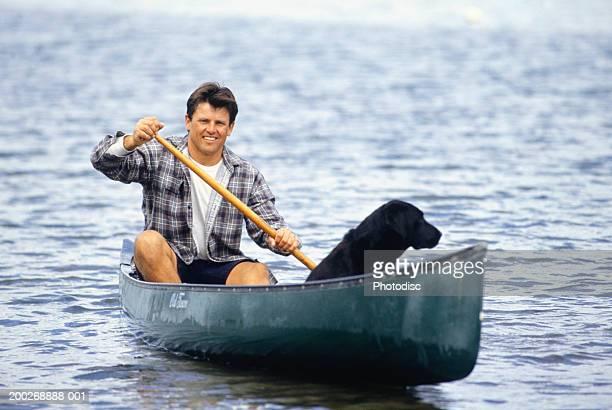 Man with dog canoeing on lake, portrait