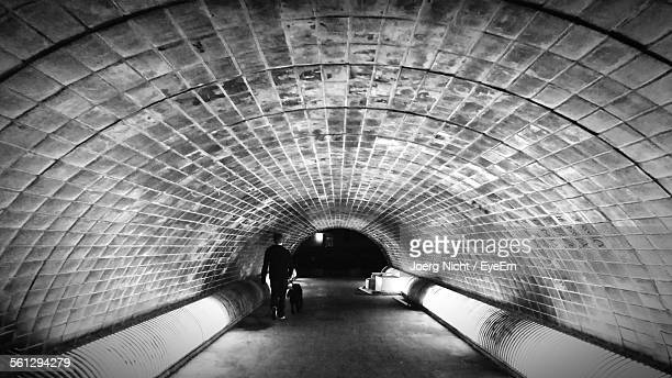 Man With Dog In Arched Walkway