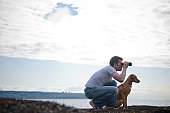 Man with dog looking through binoculars to ocean.