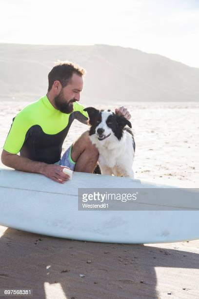 Man with dog putting paraffin on his surfboard on the beach