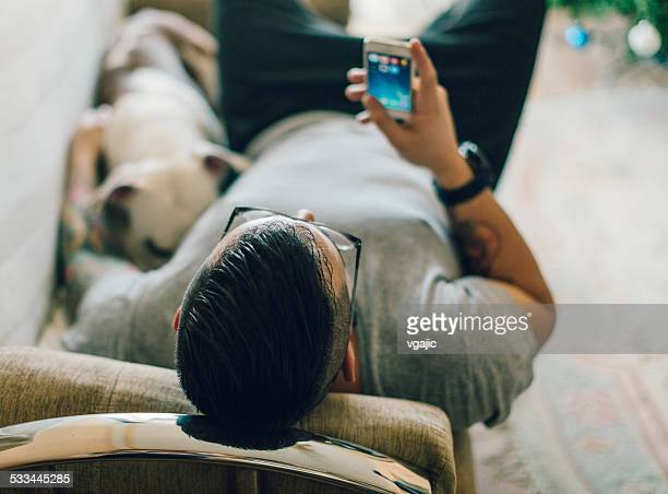 Man with dog texting.