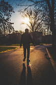 Man with dog walking on in the park against sky during sunset. Yorkshire Terrier