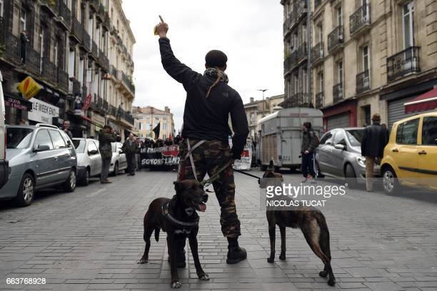 A man with dogs gestures during a demonstration against French farright candidate for the French presidential election Marine Le Pen as she holds a...