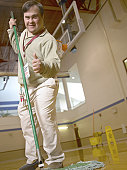 Man With Down Syndrome Sweeping A Gymnasium Floor And Giving A Thumbs Up