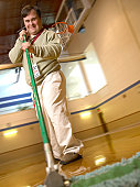 Man With Down Syndrome Sweeping A Gymnasium Floor And Smiling