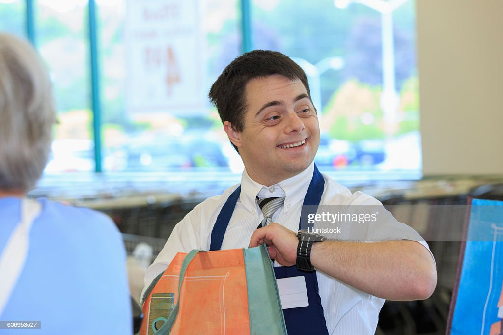 Man with Down Syndrome working at a grocery store with a customer