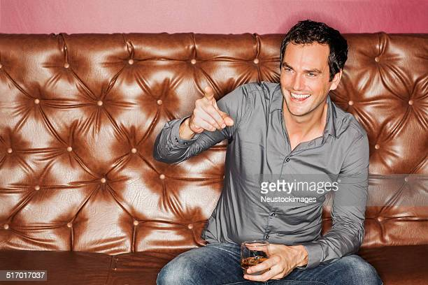 Man With Drink Pointing While Sitting On Sofa In Nightclub