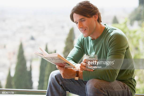 Man with drink reading on balcony