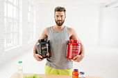 Athletic man holding bottles with sports nutriton in the white gym interior