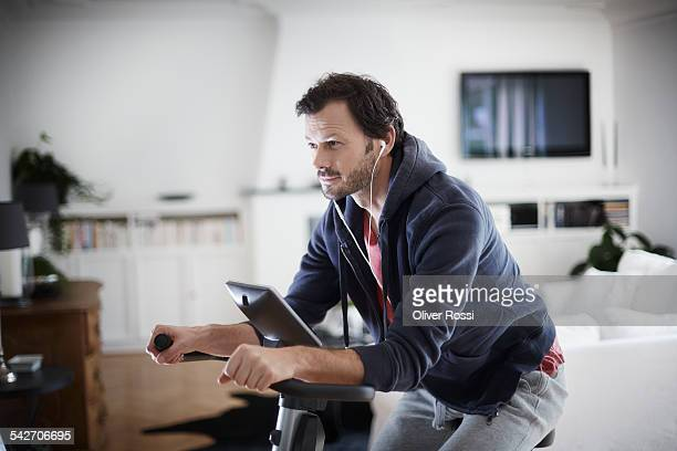 Man with earbuds on exercise bike at home